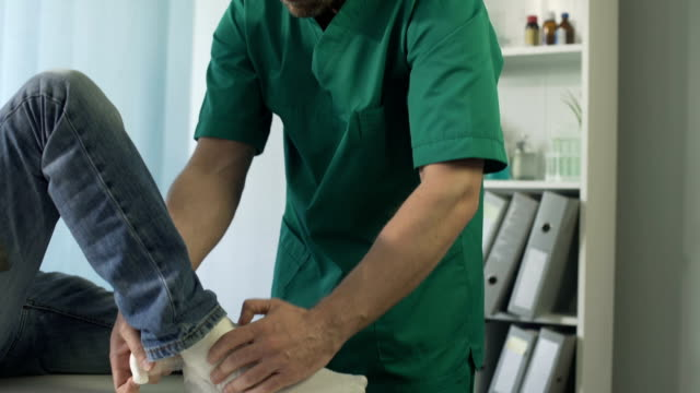 Physical therapist putting cast gypsum on a patient's broken leg, healthcare video