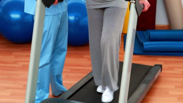 vídeos de stock e filmes b-roll de fisioterapeuta mostrando paciente como utilizar tapete rolante - aparelho de musculação