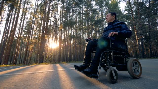 vídeos de stock, filmes e b-roll de deficiente físicos do homem está se movendo em uma cadeira de rodas alimentada ao longo da estrada - acessibilidade