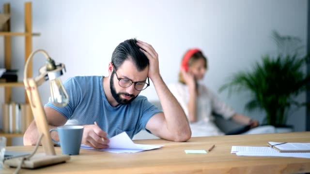 Physically exhausted young man struggling with project at home video
