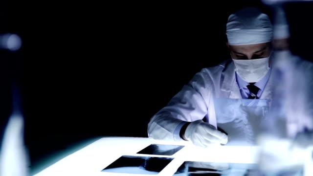 stockvideo's en b-roll-footage met physician examining x-ray bad news concept dark room - alleen één mid volwassen man