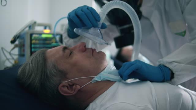 stockvideo's en b-roll-footage met arts geeft een beademingsapparaat aan een patiënt tijdens pandemie. - ventilator bed