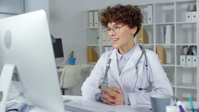 vídeos y material grabado en eventos de stock de médico que da consulta en línea usando el ordenador - receta instrucciones