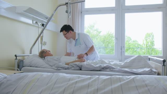 vidéos et rushes de médecin interagissant avec le patient âgé dans le service d'hôpital - infirmier