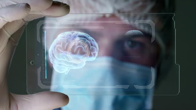 vídeos y material grabado en eventos de stock de un médico, cirujano, examina un tecnológico placa holográfica digital representa el cuerpo del paciente, pulmones corazón, músculos, huesos. - futurista