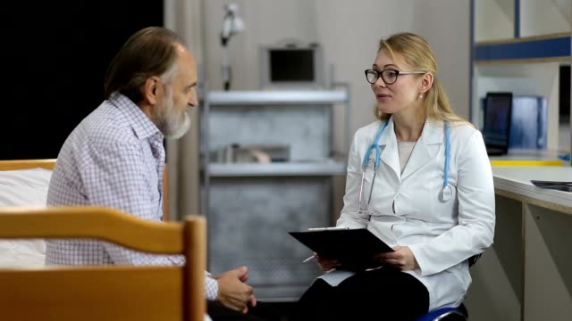 Physician telling good medical results to patient Friendly woman doctor with clipboard and in spectacles talking with senior male patient at hospital office. Positive female physician with stethoscope in lab coat explaining good medical results and giving treatment advice to happy elderly man. morality stock videos & royalty-free footage