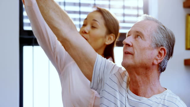 Physiotherapist assisting senior man with hand exercise 4k video