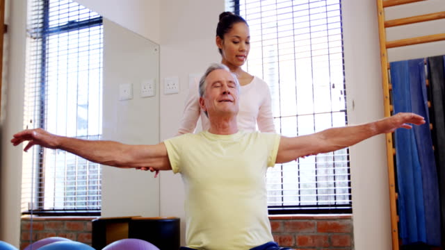 Physiotherapist assisting senior woman with hand exercise 4k video