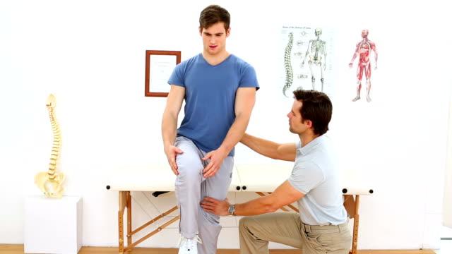 Fisioterapeuta verificando joelho de feridos paciente - vídeo