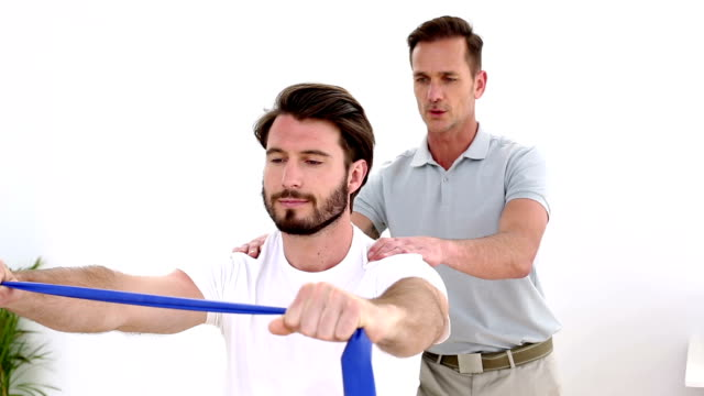Physiotherapist checking patient pulling a resistance band shoulders video