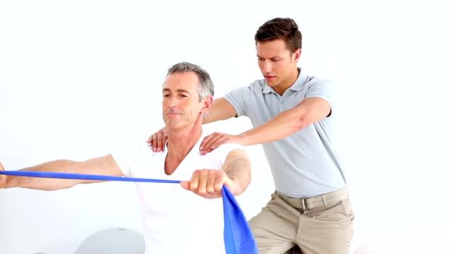 Fisioterapeuta verificando paciente sênior alongamento blue Fita de Resistência - vídeo