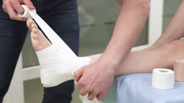 Physiotherapist doing tibia joint taping. Ankle joint pain therapy Physiotherapist doing tibia joint taping. Ankle joint pain therapy ankle stock videos & royalty-free footage