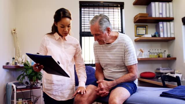 Physiotherapist examining patients knee 4k video