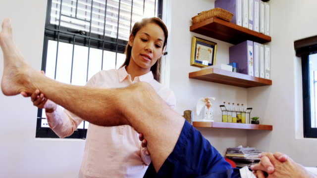 Physiotherapist examining patients knee 4k Physiotherapist examining patients knee in clinic 4k knee stock videos & royalty-free footage