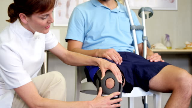 Physiotherapist examining patient's knee Physiotherapist examining patient's knee in clinic orthopedic equipment stock videos & royalty-free footage