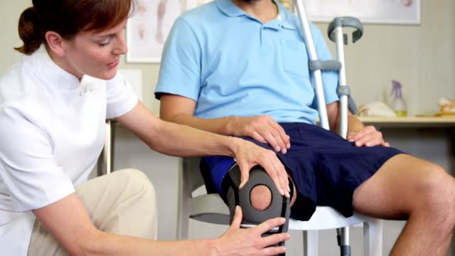 Physiotherapist examining patient's knee video