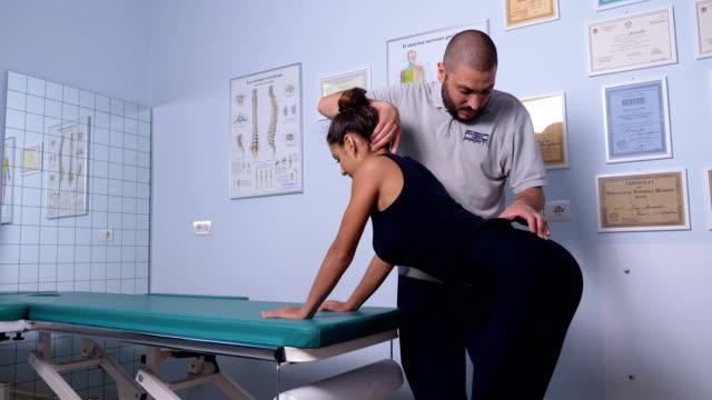 physiotherapeut examiningyoung patienten zurück haltung - hüfte stock-videos und b-roll-filmmaterial