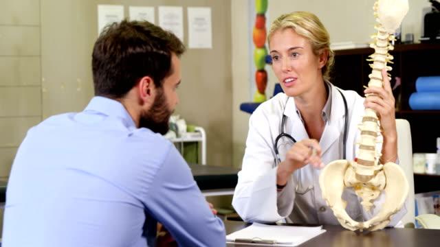 vidéos et rushes de physiothérapeute expliquant un modèle de colonne vertébrale au patient  - expliquer