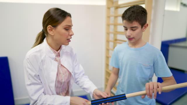 vídeos de stock, filmes e b-roll de fisioterapeuta explica à paciente como usar uma barra para exercício de ombro - ortopedia