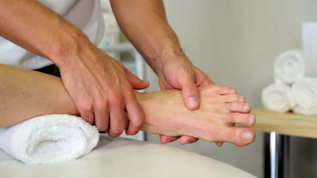 Physiotherapist giving foot massage to a female patient video