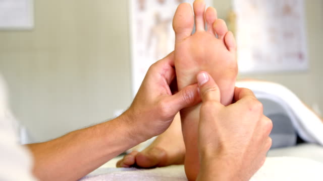 Physiotherapist giving foot massage to a woman video