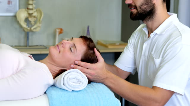 Physiotherapist giving head massage to a woman video