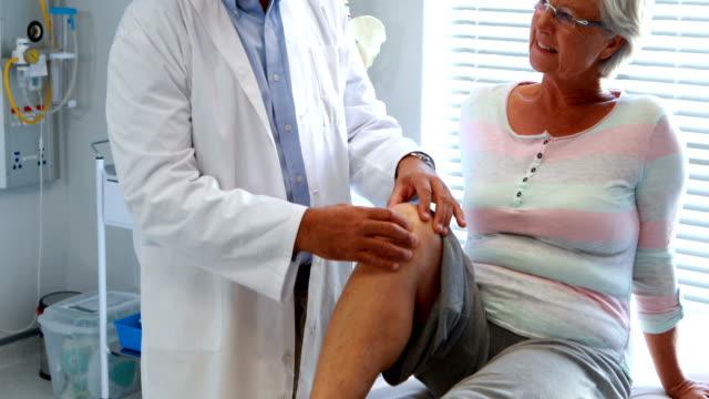 vídeos de stock, filmes e b-roll de fisioterapeuta que dá a terapia do joelho à mulher sênior - ortopedia