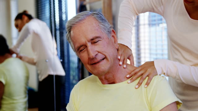 Physiotherapist giving neck massage to senior patient 4k video