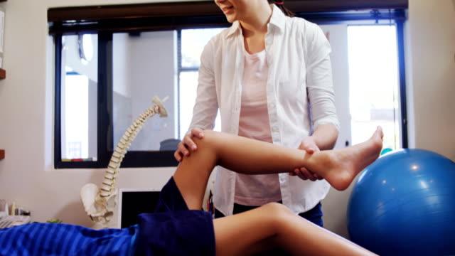 vídeos y material grabado en eventos de stock de fisioterapeuta dando fisioterapia al niño 4k - quiropráctico