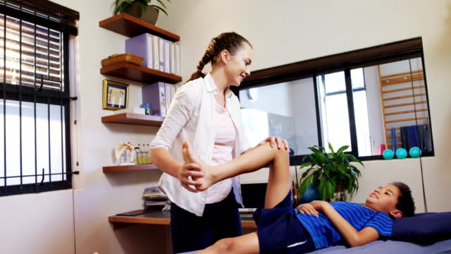 Physiotherapist giving physical therapy to the boy 4k video