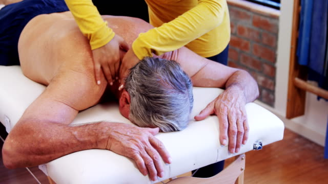 Physiotherapist giving shoulder massage to a senior man 4k video