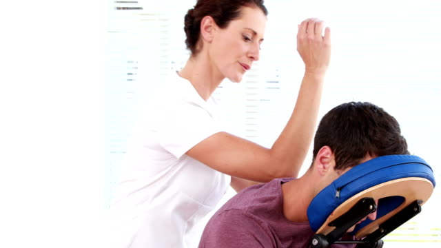 Physiotherapist giving shoulder massage to patient video