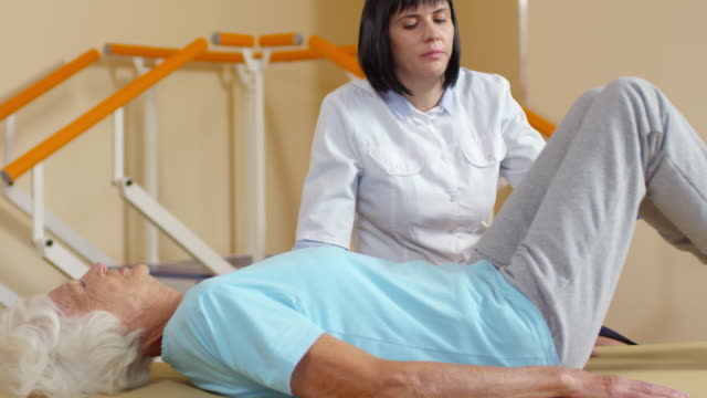 physiotherapist helping elderly patient doing exercise - torace umano video stock e b–roll