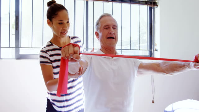 Physiotherapist helping patient in performing exercise with resistance band 4k video