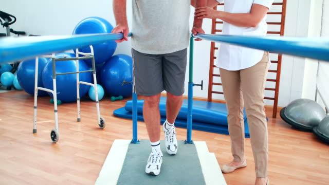 vídeos de stock e filmes b-roll de physiotherapist ajudando paciente andar com barras paralelas - melhoria