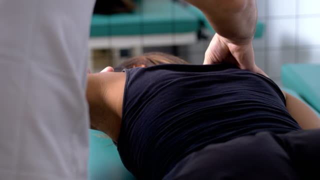 physiotherapist massages the patient's shoulder- physiotherapy session - physical therapy стоковые видео и кадры b-roll