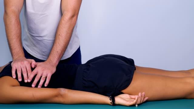 sjukgymnast massage med tryck på baksidan av en patient - massageterapeut bildbanksvideor och videomaterial från bakom kulisserna