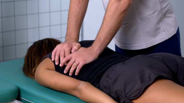 physiotherapist massages with pressure the back of a patient - chiropractor stock videos and b-roll footage