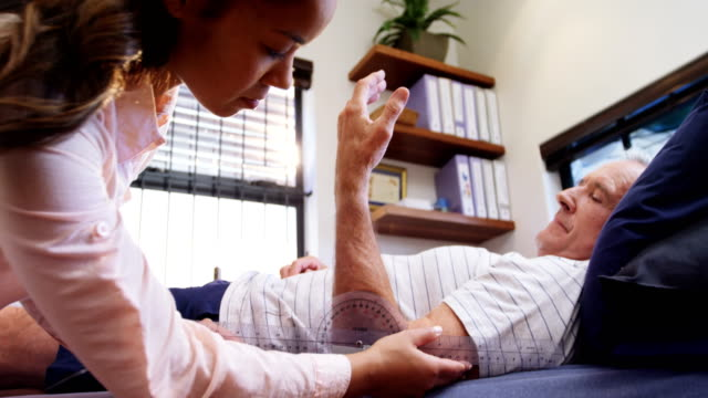 Physiotherapist measuring patient hand with medical ruler 4k video