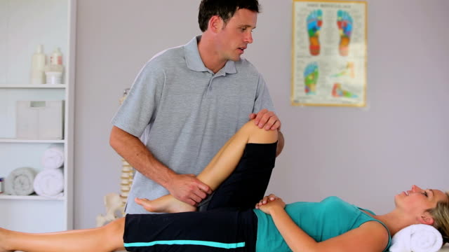 Physiotherapist moving his patients knee video