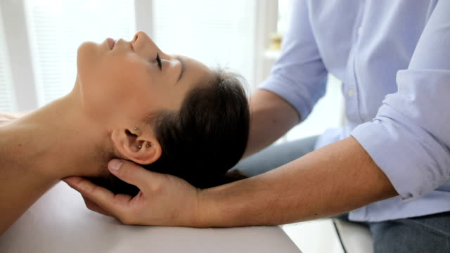 vídeos y material grabado en eventos de stock de fisioterapeuta presionando atrás de la cabeza de la mujer - quiropráctico