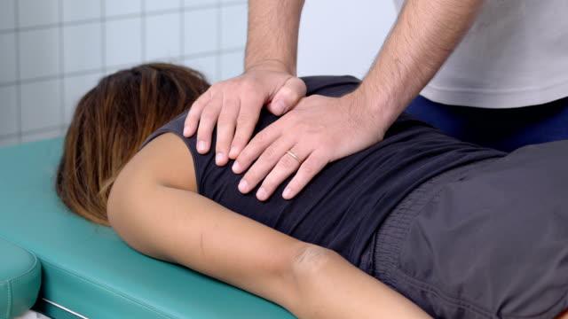 理学療法士は、患者の背骨に圧力をかける - カイロプラクター点の映像素材/bロール