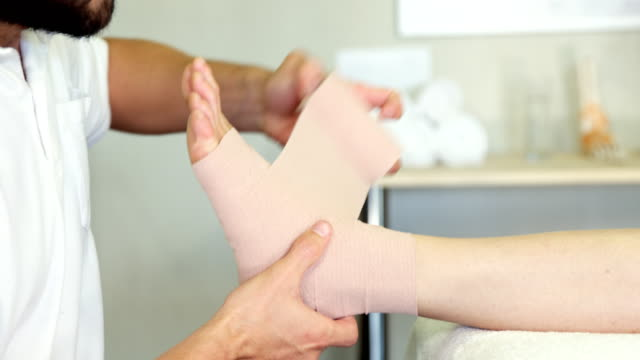 Physiotherapist putting bandage on injured feet of patient video