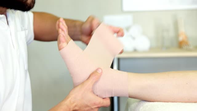 Physiotherapist putting bandage on injured feet of patient Physiotherapist putting bandage on injured feet of patient in clinic ankle stock videos & royalty-free footage