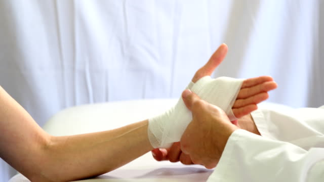 Physiotherapist putting bandage on injured hand of patient video