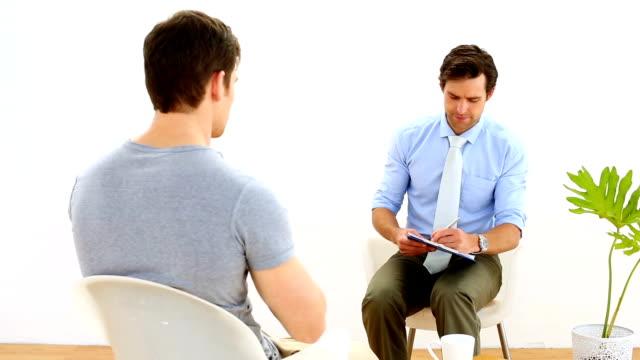 Fisioterapeuta conversando com o paciente com dor no pescoço - vídeo
