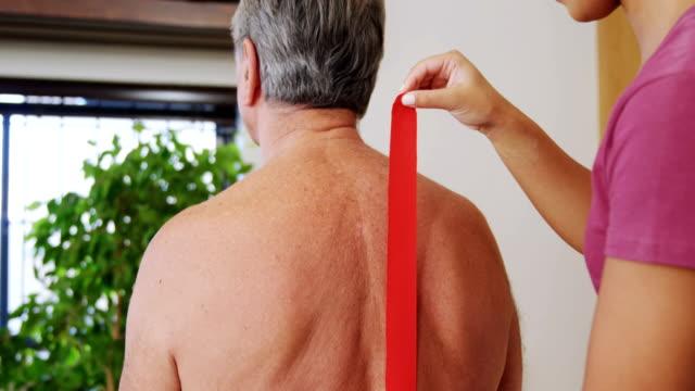 Physiotherapist sticking tape on senior patient back 4k video
