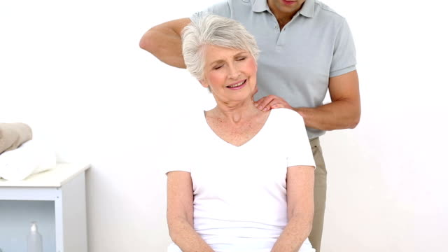 Sênior e fisioterapeuta Alongando seus pacientes pescoço - vídeo