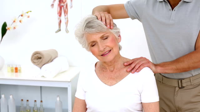 Physiotherapist stretching senior patients neck video