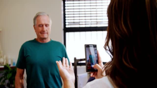 physiotherapeut unter bild der ältere mann mit handy 4k - fotografieren stock-videos und b-roll-filmmaterial